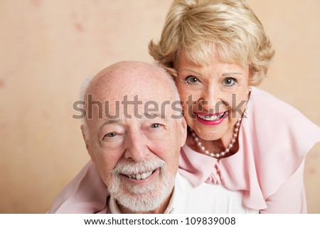 Closeup of good looking senior couple.  Shallow depth of field with focus on husband in foreground.