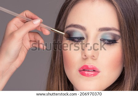closeup of gorgeous blond young woman getting eye makeup done looking down - stock photo