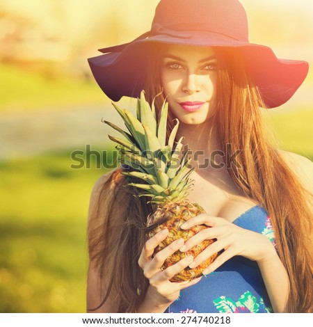 Closeup of gorgeous fashionable young blonde woman in bohemian style in blue floral dress and fedora hat holding pineapple. Square format, retouched, filter applied, vibrant colors. - stock photo