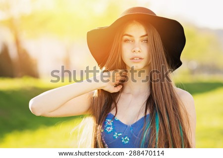 Closeup of gorgeous young woman in blue dress and fedora hat. Beautiful girl posing outdoors on sunny summer day. Horizontal, retouched, vibrant colors. - stock photo
