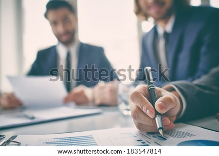 Closeup of graphs and chart analyzed by business people - stock photo