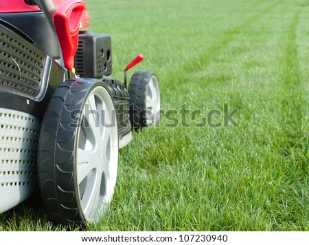 Closeup of grassmower mowing the grass - stock photo