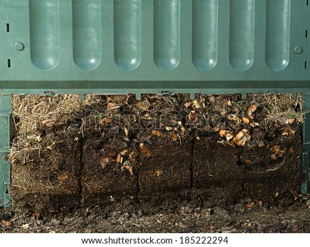 Closeup of green plastic compost bin with lower part removed to show advanced soil decomposition process - stock photo