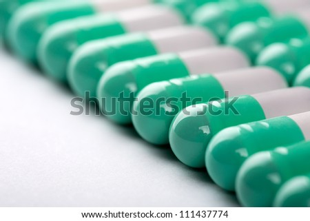 Closeup of green-white pills in a row - stock photo
