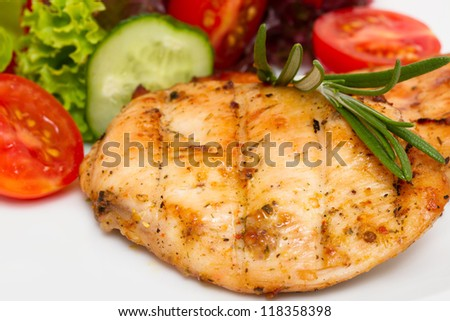 Closeup of grilled chicken fillet with vegetable salad