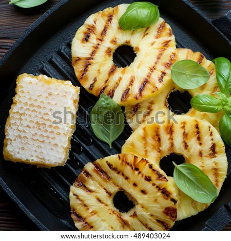 Closeup of grilled pineapple slices with addition of honey