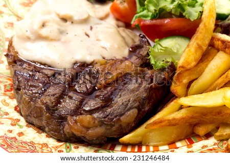 Closeup of grilled rib-eye beef steak served with mushroom sauce, salad and potato chips.