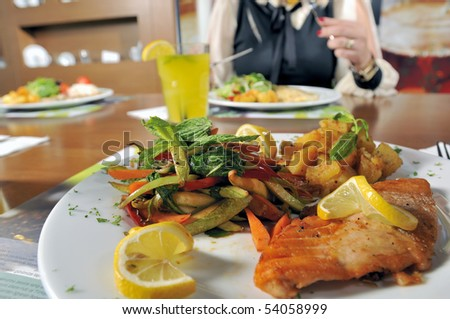 Closeup of grilled salmon fillet with background person at a restaurant.