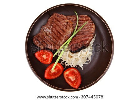 closeup of grilled steak with pasta and tomatoes on dark plate isolated over white background - stock photo
