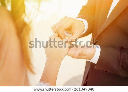 Closeup of groom putting a wedding ring on wife's hand. Closeup of heterosexual couple's hands on sunny day. Horizontal, mild retouch, warm colors.  - stock photo