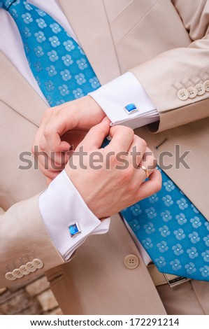 closeup of groom's arms fixing his blue cufflinks - stock photo
