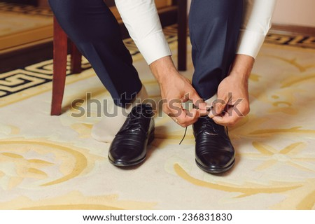 closeup of groom's hands tying laces
