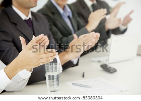 closeup of group of business people applauding at a meeting - stock photo