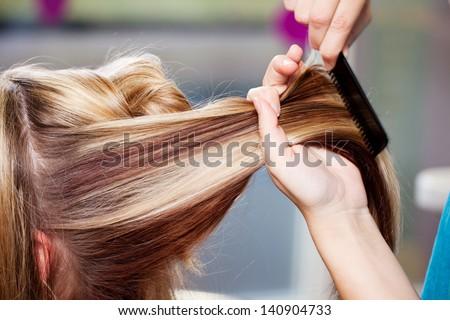 Closeup of hair dresser combing client's hair in salon