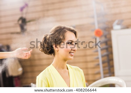 Closeup of hairdresser's hands using hairspray on client's hair at salon. - stock photo