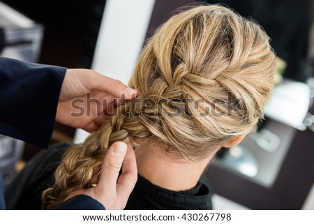 Closeup Of Hairstylist's Hands Braiding Client's Hair