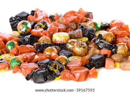 Closeup of Halloween candy -- mostly wrapped in orange and black.  Isolated on white.