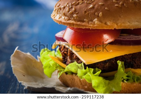 Closeup of hamburger on paper and blue table - stock photo