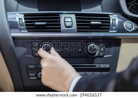 Closeup of hand adjusting the air conditioner button in the car