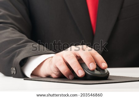 Closeup of hand and mouse, suit and tie. - stock photo