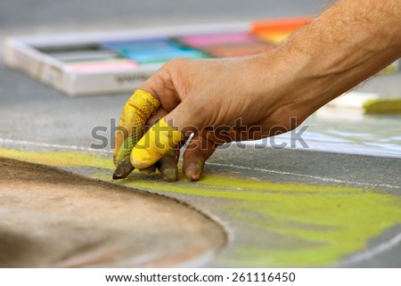 Closeup of hand drawing chalk art at fall festival - stock photo