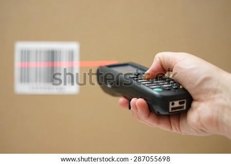 closeup of hand holding bar code scanner and scanning code on cardboard box - stock photo