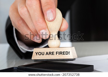 Closeup of hand holding rubber stamp with You Are Fired sign at table in office - stock photo