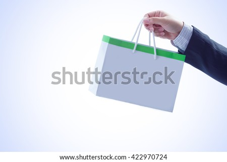closeup of hand holding shopping bag on white background - stock photo