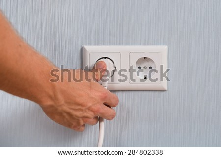 Closeup Of Hand Inserting An Electrical Plug Into A Wall Socket - stock photo