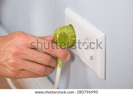 Closeup Of Hand Inserting Green Electrical Plug Into A Wall Socket - stock photo