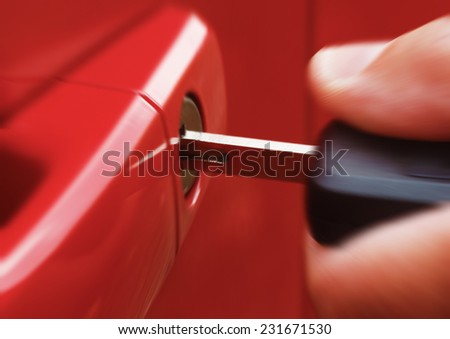 Closeup of hand inserting key into car lock with zoom blur - stock photo