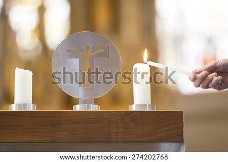Closeup of hand lighting candle by sculpture in church - stock photo