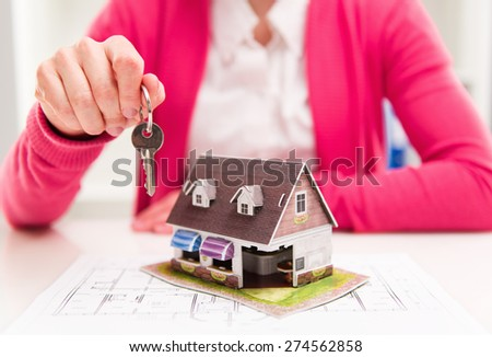 Closeup of hand of real estate agent offering keys of new house to buyer holding keyring. Shallow depth of field.    - stock photo