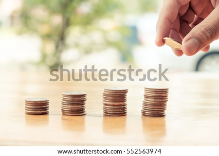 Closeup of hand put Coins to stack of coins,Concept Saving money. Saving money back car