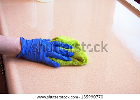 closeup of hand with purple latex glove cleaning  kitchen counter top with green microfiber cloth