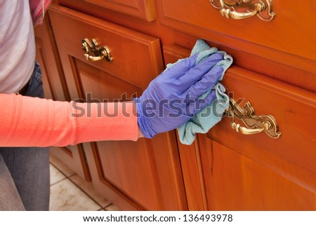 closeup of hand with purple latex glove cleaning  wooden cabinet with green microfiber cloth - stock photo