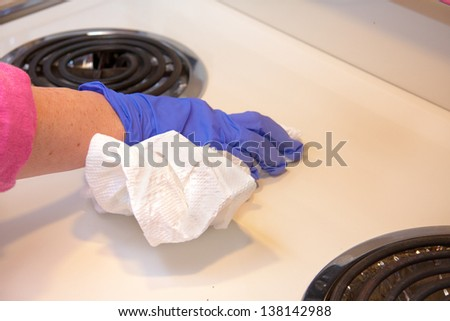 closeup of hand with purple latex gloves cleaning  stove with paper towels - stock photo