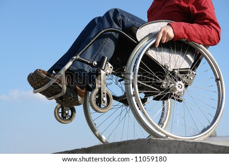 Closeup of handicapped woman balancing on wheelchair by the concrete kerb over blue sky - stock photo