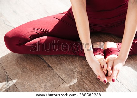 Closeup of hands and legs of young woman doing yoga barefoot - stock photo