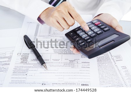 Closeup of hands counting taxes using calculator