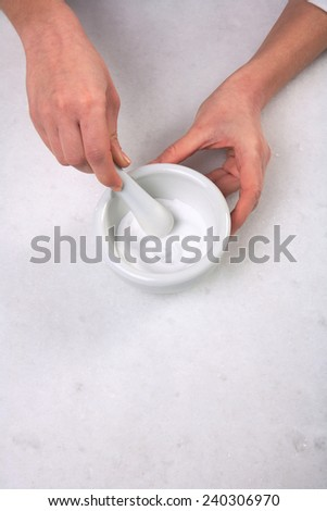closeup of  hands crushing powder on mortar with pestle