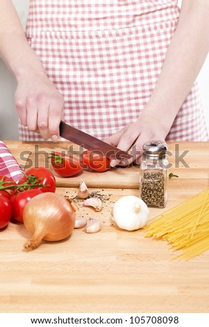 closeup of hands cutting vegetables for pasta - stock photo