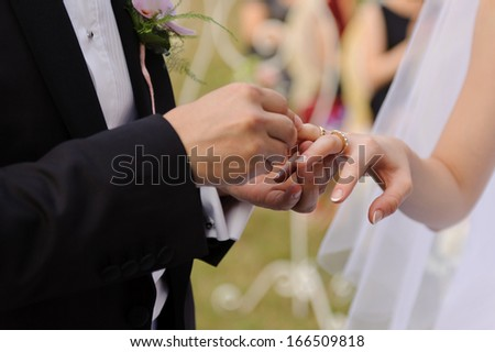 closeup of hands exchanging wedding rings