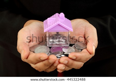 Closeup of hands holding coins and house shape  - stock photo