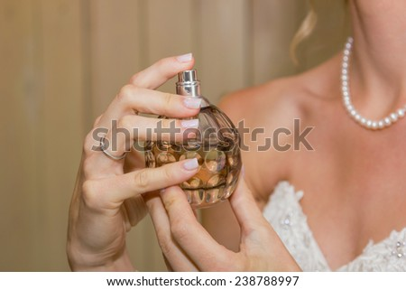 closeup of hands holding perfume bottle