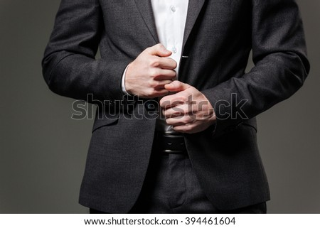 Closeup of hands of handsome young businessman in black suit and white shirt over grey background - stock photo