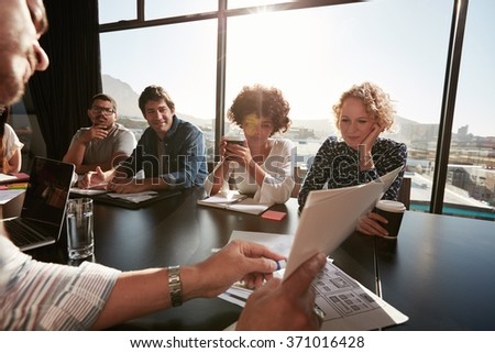 Closeup of hands of young male executive discussing business plan with colleagues. Creative people meeting in conference room. - stock photo