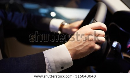 Closeup of hands on a steering wheel - stock photo