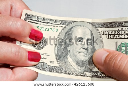 Closeup of hands pulling a hundred dollar banknote - stock photo