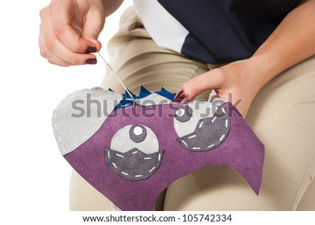 closeup of hands sewing fabric on white background - stock photo